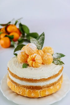 Cake with fresh mandarin and leaves on a white background.