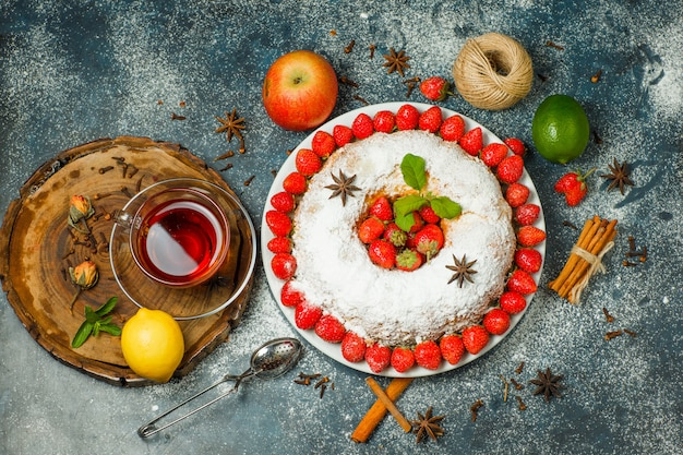 Cake with fruits, strainer, tea, thread, spices, sugar, herbs in a plate on wooden board and stucco background, top view.