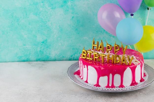 Cake with glaze and candles high angle