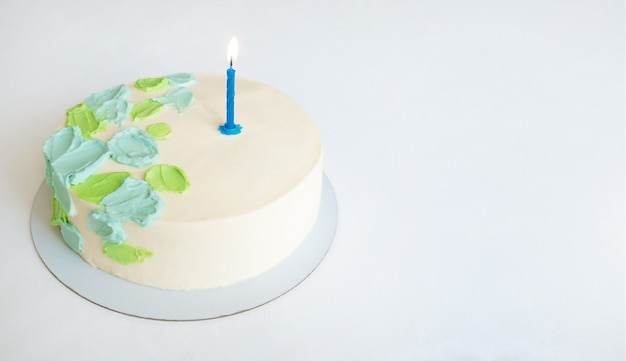 Cake with green and blue abstract decor and one candle. copy space.