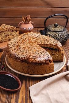 Cake with jam raisin sesame cinnamon tea pot side view