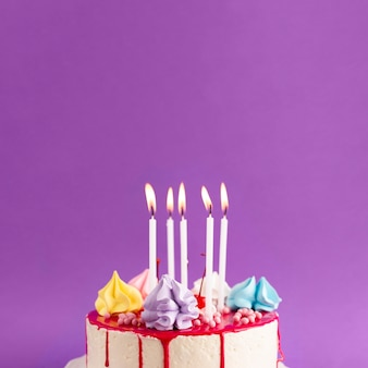 Cake with lit candles on purple background