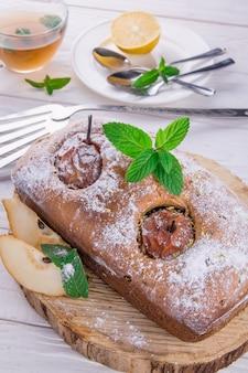 木製の背景に梨とミントのケーキ