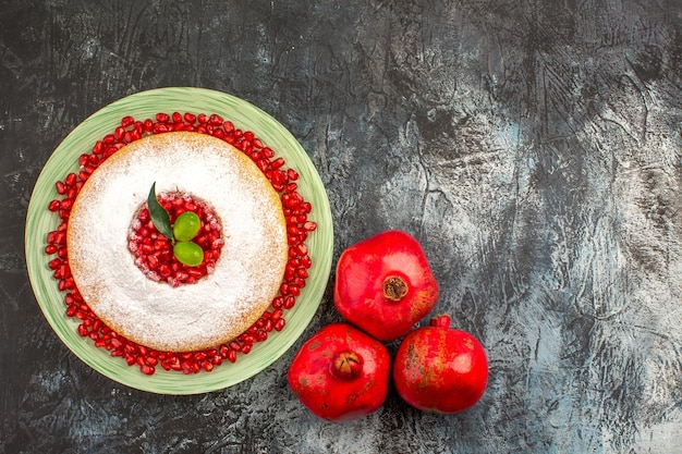 Cake with pomegranate a cake with seeds of pomegranate and three pomegranates