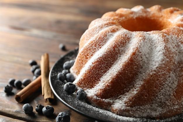 Торт с сахарной пудрой и черникой на деревянном фоне, место для текста