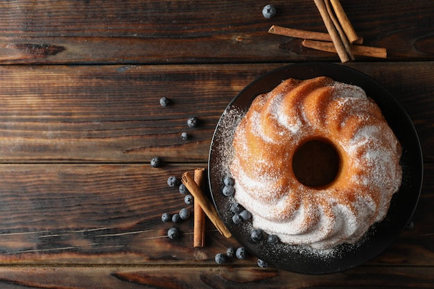 Cake with powder sugar and blueberry on wooden background, top view