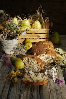 Cake with raisins and pears on wooden table in rustic style