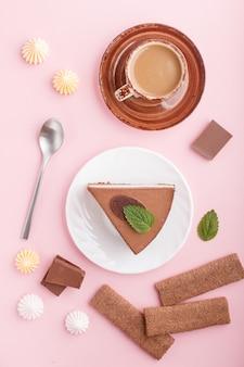 Торт с суфле из молочно-шоколадного крема с чашкой кофе, безе на розовой пастельной поверхности. вид сверху.