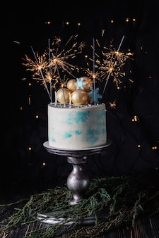 Cake with sparklers - decorated christmas cream cake, burning sparkler on dark background