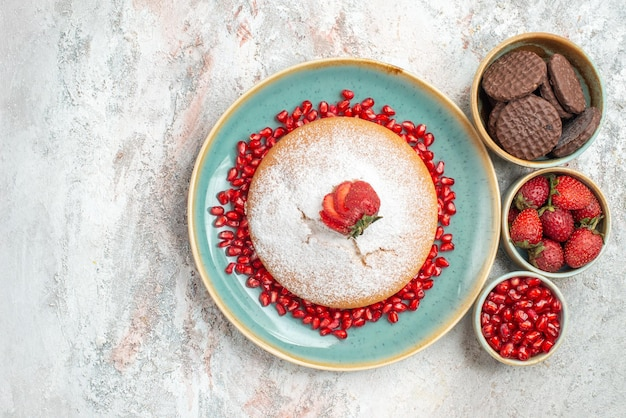 Cake with strawberries cake with seeds of pomegranate and chocolate cookies