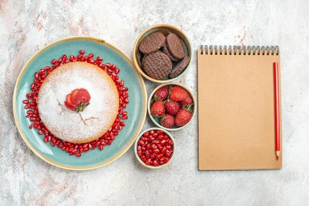 イチゴのケーキノートとペンの横にイチゴのケーキ