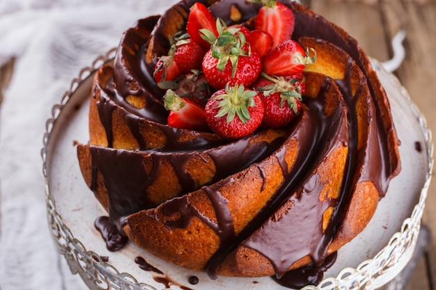 Cake with strawberries and chocolate glaze on the base.