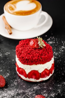 Cake with strawberries and cup of cappuccino on the table