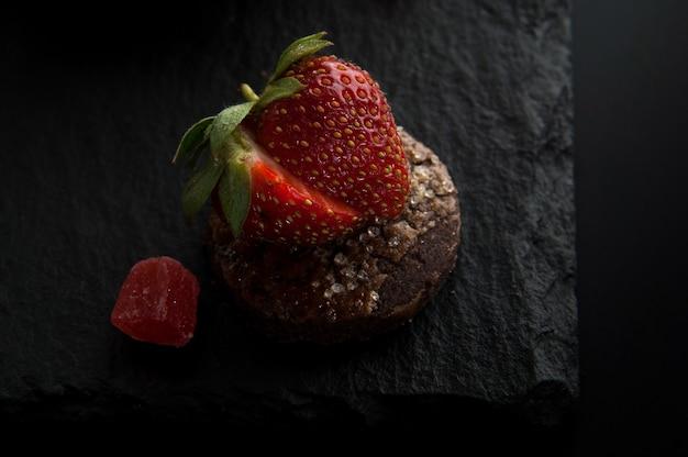暗い背景の装飾的な石にイチゴとケーキ