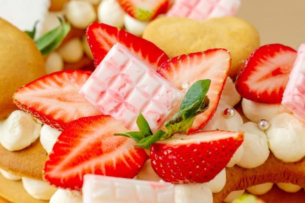 딸기, 핑크 밀크 초콜릿 바, 은색 뿌리, 바닐라 크림 및 심장 채프 쿠키와 케이크를 닫습니다.