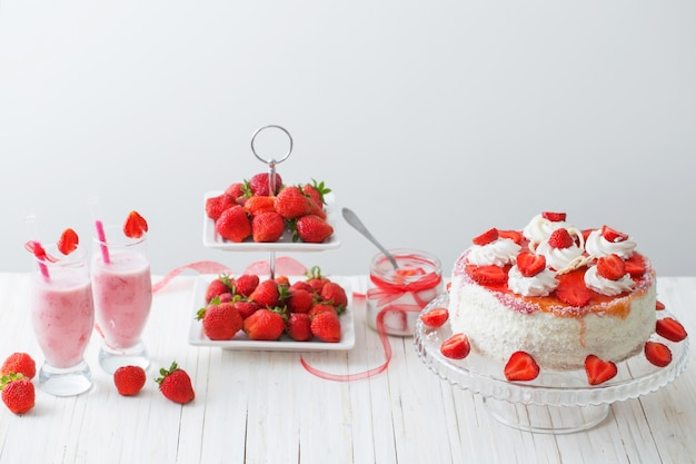Cake with strawberries on wooden table