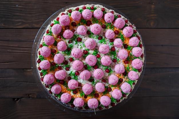 Торт с сахарной вишней на деревянном столе (вид сверху)