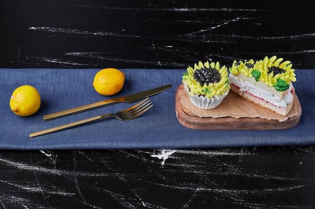 木製の大皿にひまわり風の装飾が施されたケーキ。