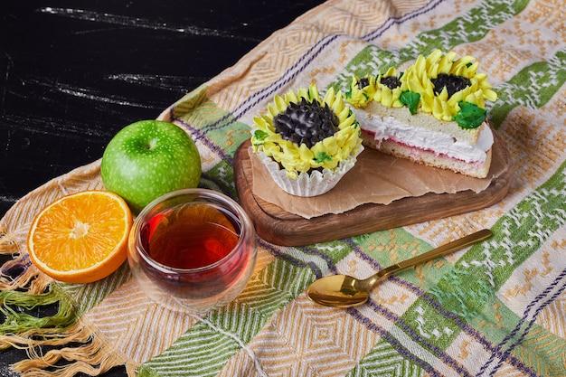 お茶と木の板にひまわり風の装飾が施されたケーキ。