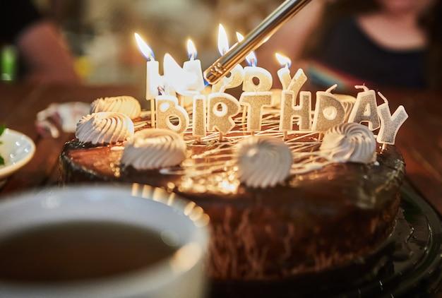 불타는 초와 함께 비문 생일 케이크.