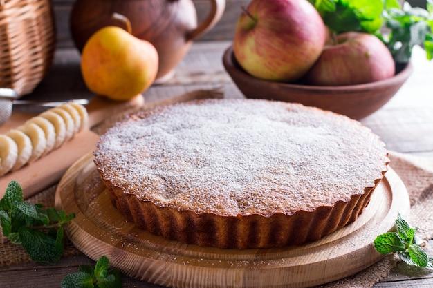 木製のクルミと粉砂糖とバナナのケーキ