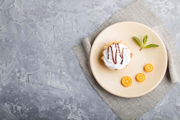 Cake with whipped egg cream on a light brown plate with kumquat and mint leaves