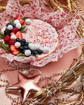 Торт со взбитыми розовыми сливками, свежей клубникой, черникой, ежевикой и малиной на розовом фоне. картинка для меню или каталога кондитерских изделий.