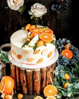 ライムとオレンジで飾られた白いクリームのケーキ
