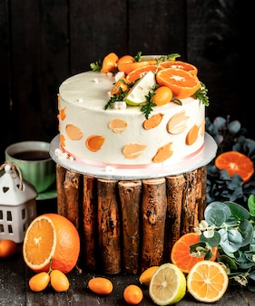 Cake with white cream decorated with lime and orange