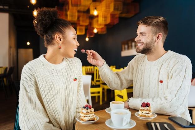 妻とケーキ。妻にケーキを与えるニットの軽いセーターを着ている思いやりのある愛情のある男