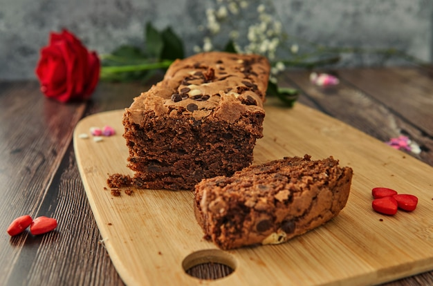 A cake on a wooden table with hearts and a rose.
