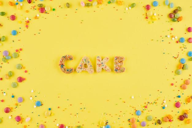 뿌리와 화려한 사탕과 설탕 쿠키로 만든 케이크 단어