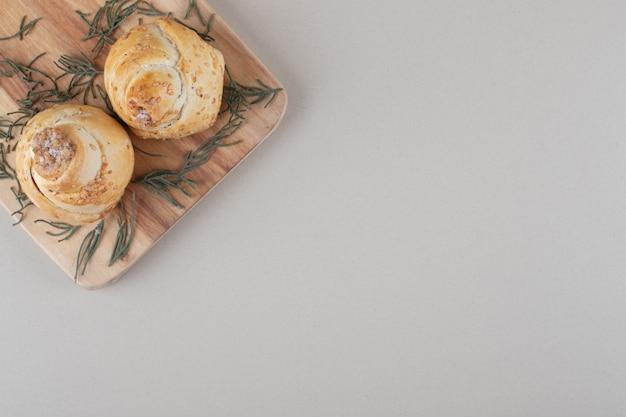 大理石の背景に松の葉で飾られたボードにナッツを詰めたケーキラッピング。
