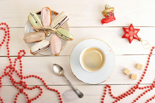 Cakes in a dish and coffee with christmas toys and beads