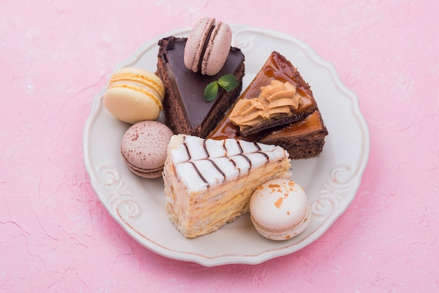 Cakes and macarons on plate with mint