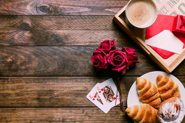 Cakes on plate near flowers and playing cards near cup of drink and letter on board