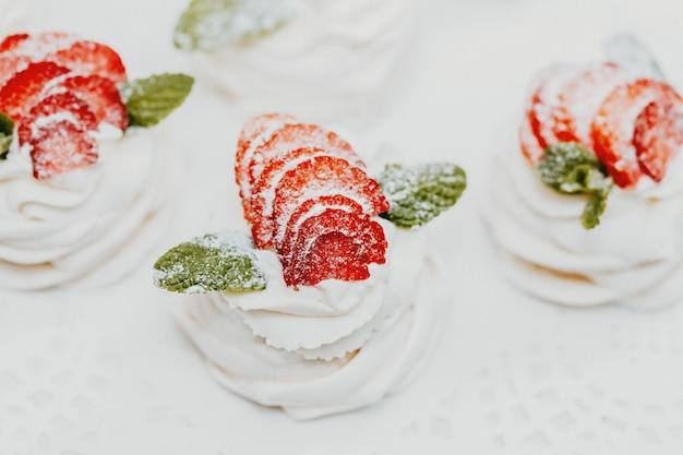 ブルーベリー、ラズベリー、ミントで飾られたクリームのケーキ。