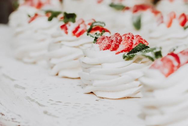 イチゴの粒子とミントで飾られたクリームのケーキ。