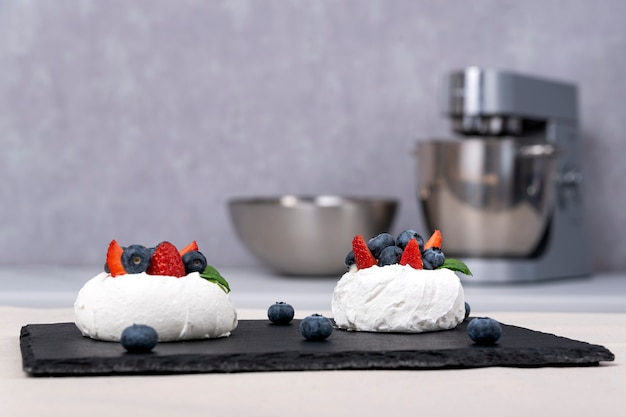 Пирожные со свежими ягодами. пирожные из безе с клубникой и черникой.