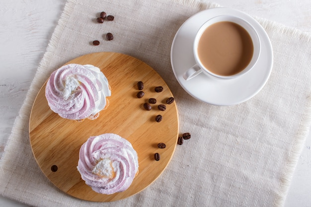 Cakes with whipped egg cream on linen napkin.