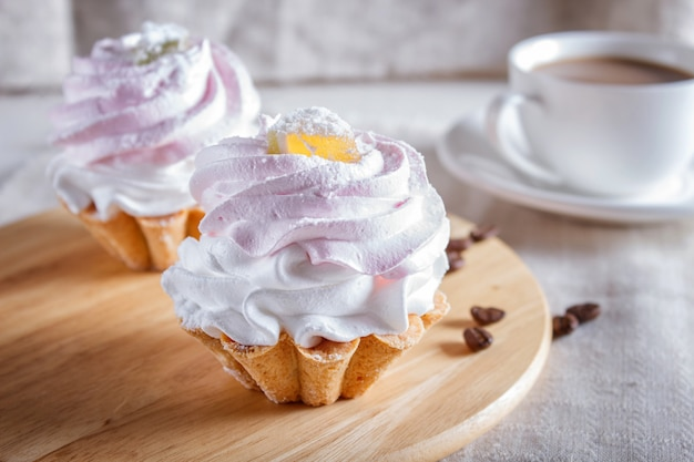 Cakes with whipped egg cream on wooden board.