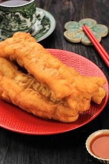 Cakwe (cakue) или китайская масляная хлебная палочка - это традиционная индонезийская еда на завтрак, которую подают в красной керамической тарелке на деревянном столе. в индонезии обычно подают в качестве топпинга из куриного отваги. закрыть вверх