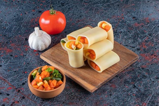 Паста calamarata с нарезанными овощами на деревянной доске.