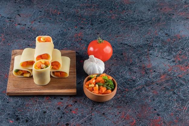 Calamarata ripiena di verdure tritate su tavola di legno.