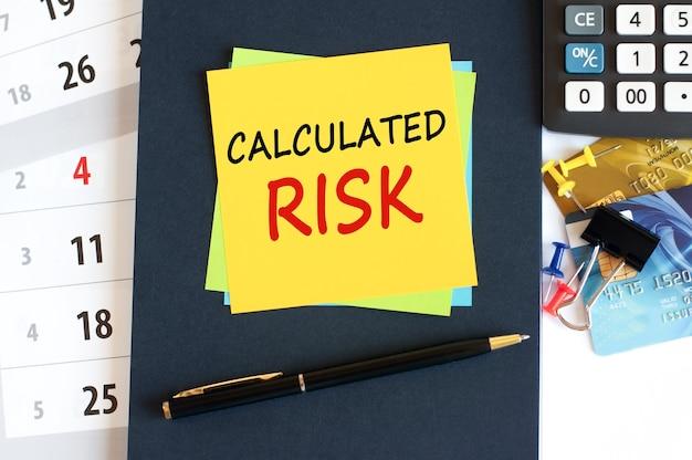計算されたリスク、青い背景の黄色い紙の正方形のテキスト。デスクトップ上のメモ帳、電卓、クレジットカード、ペン、文房具。ビジネス、金融、教育の概念。セレクティブフォーカス。