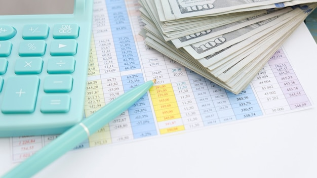 On the calculated white sheet lying dollars calculator and pen