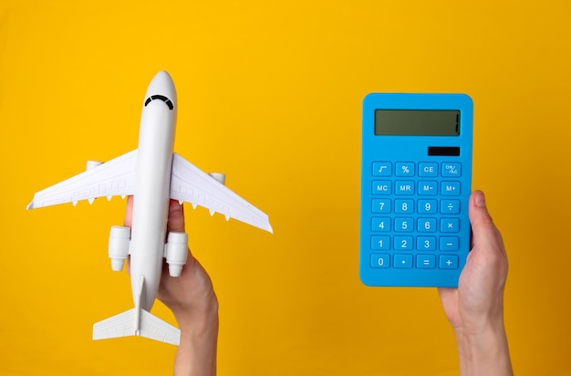 Calculation of the cost of air travel, travel. hand holds blue calculator and figurine of passenger plane on yellow.