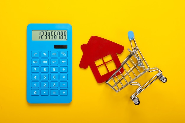 Calculation of the cost of buying or selling a home. calculator, figurine of a house in a shopping trolley on yellow background. top view. flat lay