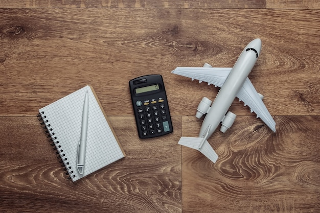 Calculation of the cost of vacation. plane figurine, calculator and notebook on wooden floor.. flat lay