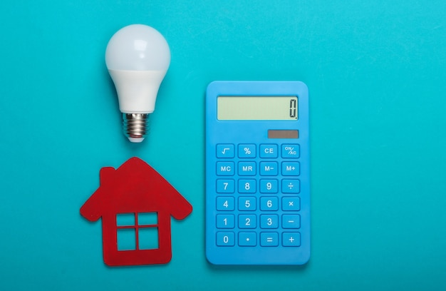エネルギー効率とコストの計算。電卓、家の置物、緑の背景に電球を導きました。上面図